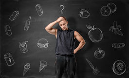 Muscled young man pondering on what to choose: junk or healthy food Royalty Free Stock Photo