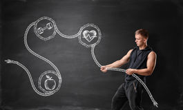 Muscled young man pulling drawn rope with apple, dumbbell and beating heart. Side view of muscled young man pulling drawn rope with apple, dumbbell and beating royalty free stock photography