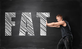 Muscled young man pushing big drawn fat word by both hands on the background of a blackboard. Losing weight and fat burning. Bodybuilding and self-improvement Stock Image