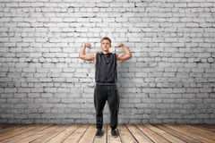 Muscled young man showing his bicep muscles on the background of white brick wall. Front view of muscled young man showing his bicep muscles on the background of Royalty Free Stock Photos