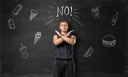 Muscled young man showing stop sign with his hands and says no to unhealthy food on the background of blackboard. Healthy lifestyle. Sportive nourishment stock images