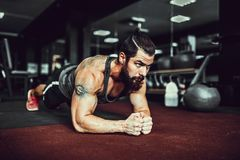 Free Muscled Young Man Wearing Sport Wear And Doing Plank Position While Exercising On The Floor In Loft Interior Stock Images - 100607234