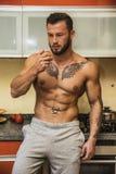 Muscleman atractivo en cocina que come la manzana Imagen de archivo