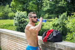 Muscleman drinking water from plastic bottle Royalty Free Stock Photos