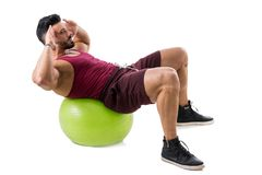 Muscleman exercising abs on an exercise ball Royalty Free Stock Photo