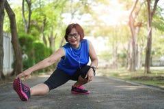 Muscles asiatiques supérieurs de bout droit de femme au parc photos stock