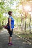 Muscles asiatiques supérieurs de cuisse de bout droit de femme au parc image stock