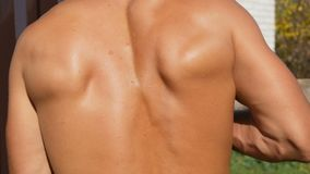 Muscles of the back of a sexy, sunburnt pumped up young worker. Sweat on back, bare torso