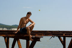 Muscles boy near the sea Royalty Free Stock Images