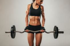 Muscles bulging on arms of woman using barbell Royalty Free Stock Images
