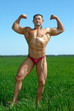 Muscles and nature. The young sportsman poses in the street showing the beefy muscles Royalty Free Stock Image