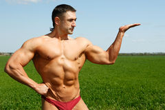Muscles and nature. The young sportsman poses in the street showing the beefy muscles Royalty Free Stock Photography