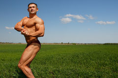 Muscles and nature. The young sportsman poses in the street showing the beefy muscles Royalty Free Stock Photos