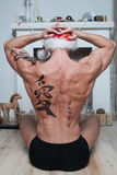 Muscly man with tattooed back Stock Images