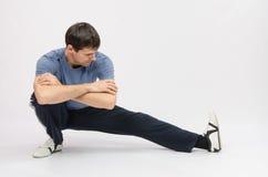 Muscoli accovacciantesi di allungamenti dell'atleta della gamba sinistra Immagine Stock