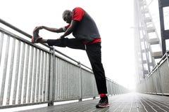 Muscoli americani neri di allungamento del corridore Fotografia Stock Libera da Diritti
