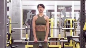 Muscoli di formazione delle spalle della bella donna castana con il bilanciere archivi video