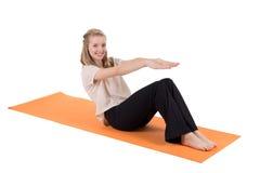 Muscoli di stomaco biondi sorridenti di addestramento della donna con le mani diritte nella parte anteriore su una stuoia Fotografia Stock