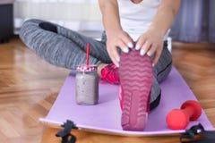 Muscolo attraente della giovane donna che allunga sulle gambe con le scarpe da tennis rosse sulla stuoia porpora di forma fisica  immagine stock