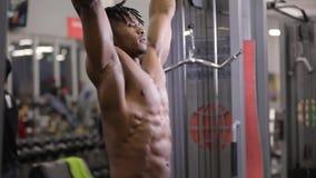 Muscolo di pompaggio dell'ABS dell'uomo afroamericano che appende sulla barra orizzontale in palestra video d archivio