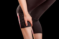 Muscolo joggermassaging del vitello di sport di lesione dell'atleta corrente della donna prima dell'allenamento nel fondo nero Immagini Stock Libere da Diritti
