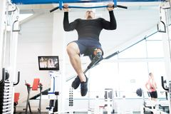 Muscular Adaptive Sportsman Using Exercise Machines in Gym. Low angle portrait of muscular sportsman with prosthetic leg doing pull ups while working out in stock images