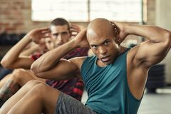 Men doing sit ups workout. Muscular african american men doing sit ups at gym with other people in background. Mature black men doing abs workout with class at stock photography