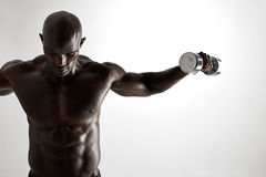 Muscular african fitness model working out with dumbbells Royalty Free Stock Photography