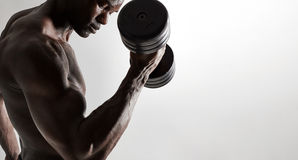 Muscular african male model lifting heavy dumbbells Stock Images