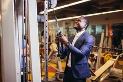 Man in suit working out in gym. Muscular african man in classic suit working out in gym doing exercises at triceps, strong male businessman Stock Images