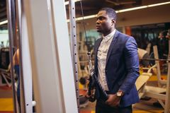 Man in suit working out in gym. Muscular african man in classic suit working out in gym doing exercises at triceps, strong male businessman Stock Image