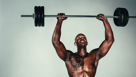Muscular african man exercising with barbell Royalty Free Stock Images