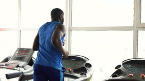 Muscular Afro-American man running on treadmill in the gym, workout, sport. Stock footage stock footage
