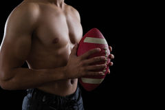Muscular American football player holding a football in his hand