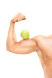 Muscular arm with an apple on the bicep Royalty Free Stock Images