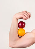 Muscular arm holding fruit Royalty Free Stock Photo