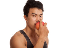 Muscular Asian man bite  red apple Stock Photography