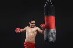 Muscular asian man boxer training with punching bag Royalty Free Stock Photo