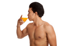 Muscular Asian man drinking orange juice. Isolated on white background Stock Images