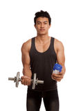 Muscular Asian man with dumbbell and whey protein shakes Stock Images