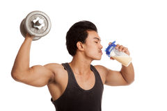 Muscular Asian man with dumbbell and whey protein shakes Royalty Free Stock Photo