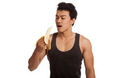 Muscular Asian man eat  peeled banana Stock Image