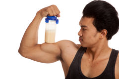 Muscular Asian man  flexing biceps with whey protein shakes Royalty Free Stock Photo