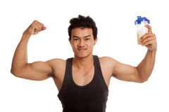Muscular Asian man  flexing biceps with whey protein shakes Royalty Free Stock Photography