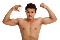 Muscular Asian man flexing biceps with white drug pill bottle. Isolated on white background Royalty Free Stock Images