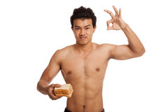 Muscular Asian man load carbs with some bread show OK Royalty Free Stock Image