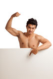 Muscular Asian man point down  flexing biceps behind  blank sign Stock Images