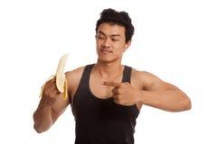 Muscular Asian man point to peeled  banana Stock Photos