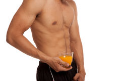 Muscular Asian man show his six pack abs with orange juice Royalty Free Stock Photos