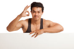 Muscular Asian man show OK  behind  blank sign Royalty Free Stock Photos